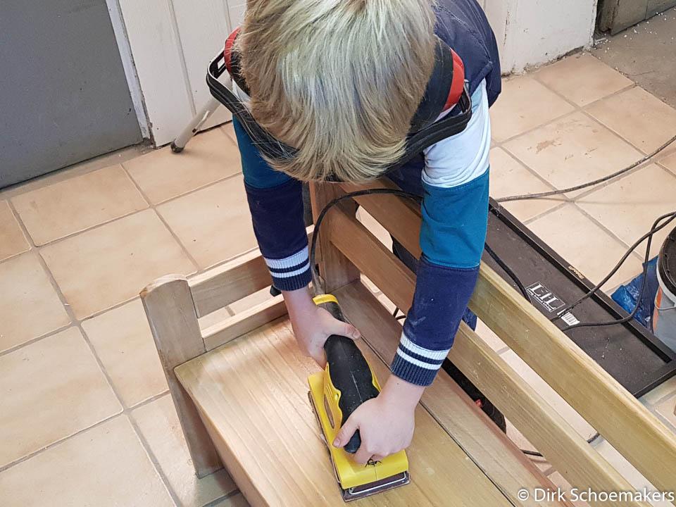 Kind schleift mit einem Schwingschleifer eine Bank ab