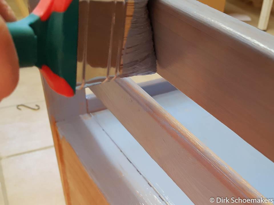 Pinsel trägt Farbe auf eine Bank auf